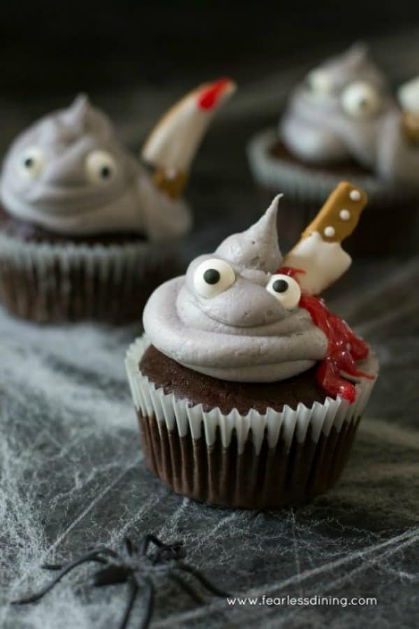 Iced cupcakes with googly eyes and a knife stuck in with red icing oozing out