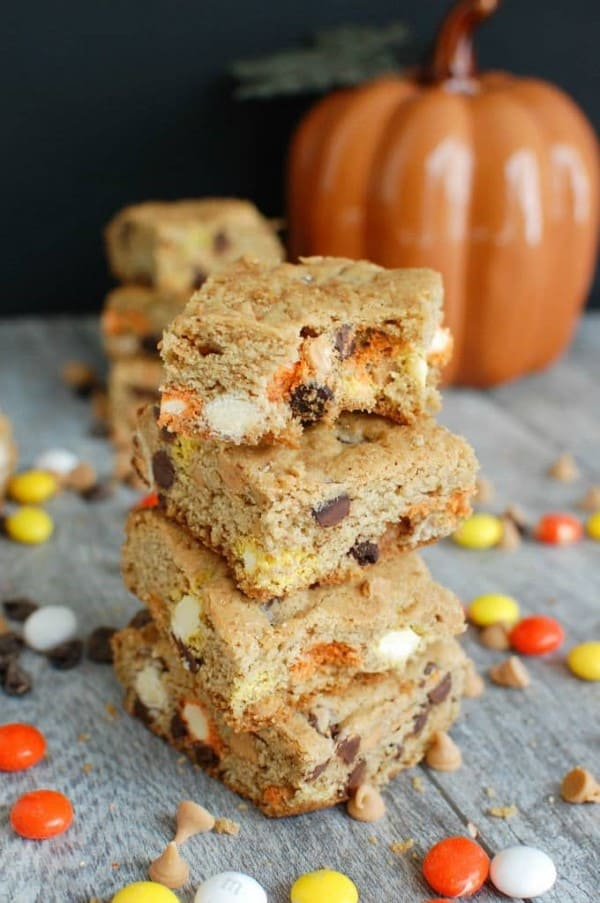 Stacked monster cookie bars with a pumpkin in the background
