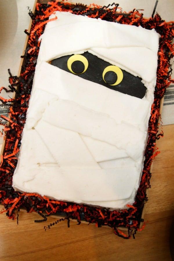 Mummy cake with paper orange and black shred around it