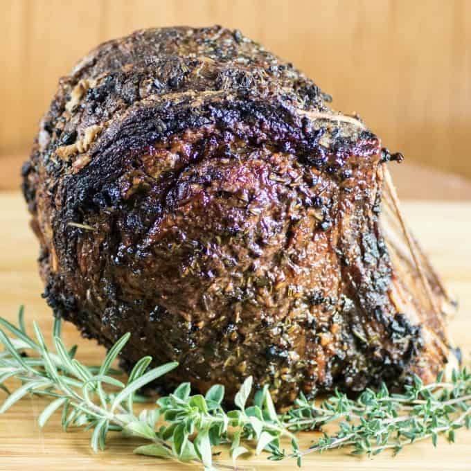 Roast Beef on a wooden cutting board with fresh herbs