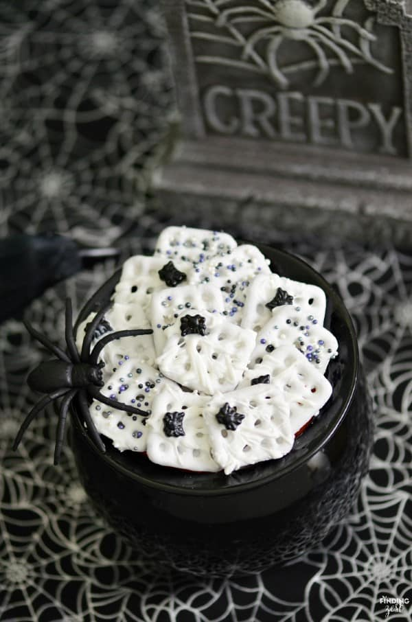 White spiderweb pretzels in a black bowl with tiny candy spiders