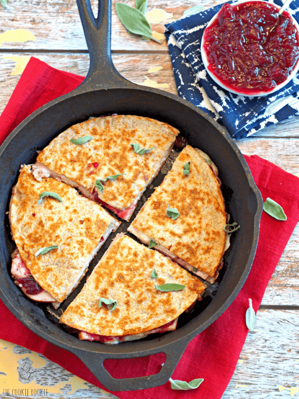 Thanksgiving leftover quesadillas in a cast iron pan with cranberries on the side
