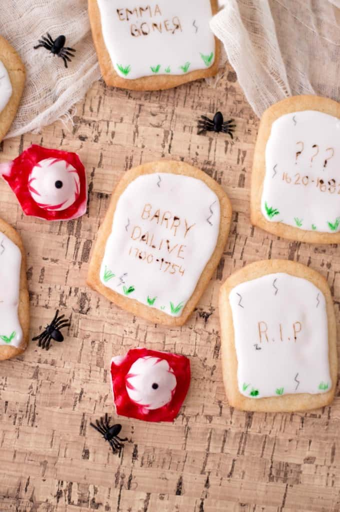 Halloween Tombstone Cookies on a cork mat with spiders and eyeballs