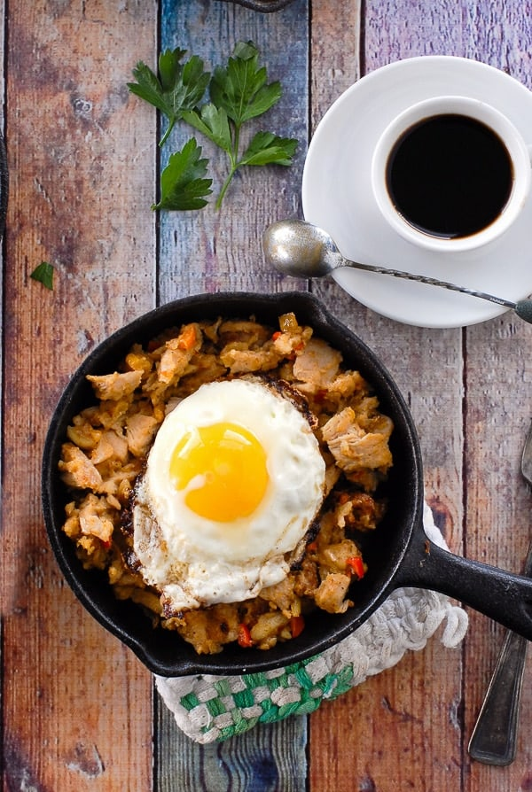 Turkey hash with a fried egg on top in a cast iron pan on a board