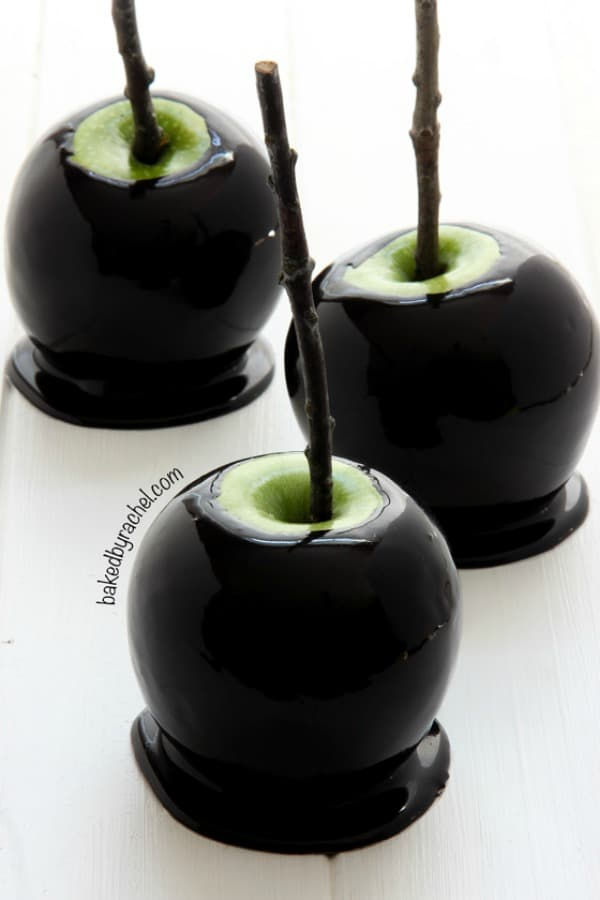 Black candy coated green apples on a stick