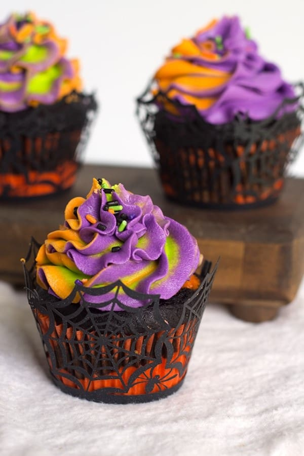 Colorfully iced Halloween cupcakes in spiderweb cupcake holders