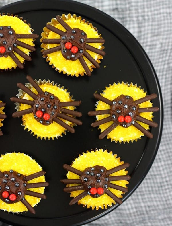 Spiders on top of yellow cupcakes