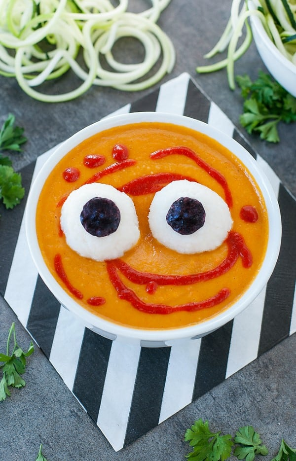 Orange soup in a white bowl with large eyeballs on a black and white napkin