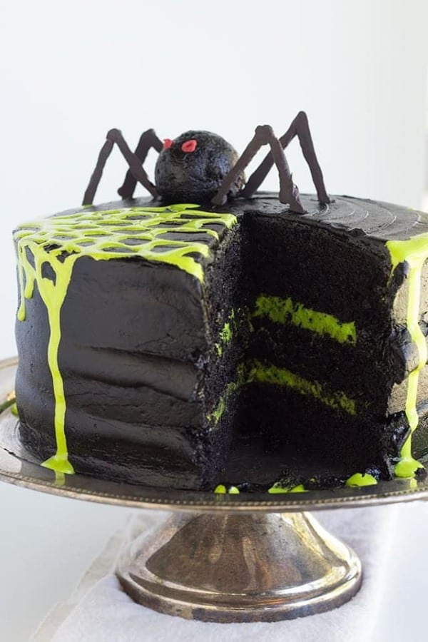 Black layered cake with green spider web and a giant spider on top