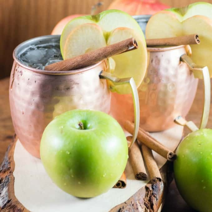 Apple Bourbon Moscow Mule in a copper mug with apple slices.