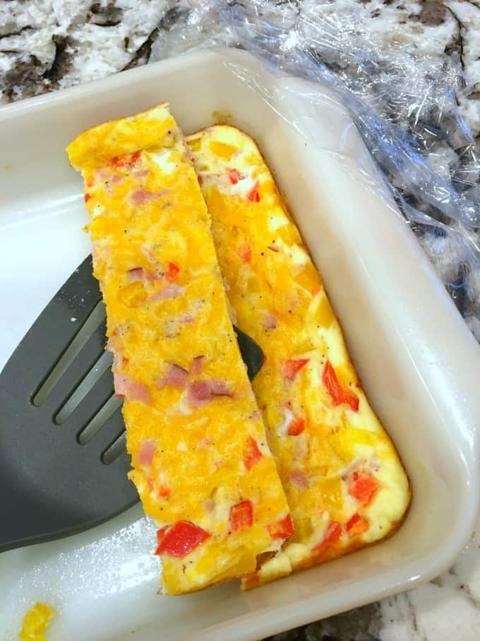 Baked omelet on a spatula from a casserole dish