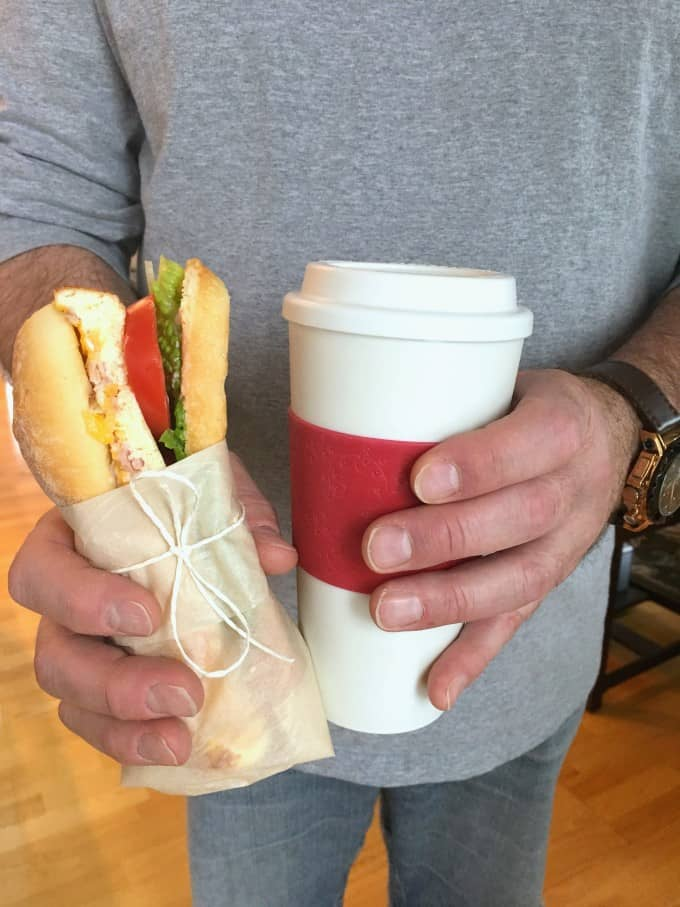Man holding a Breakfast Sandwich To Go and a coffee cup