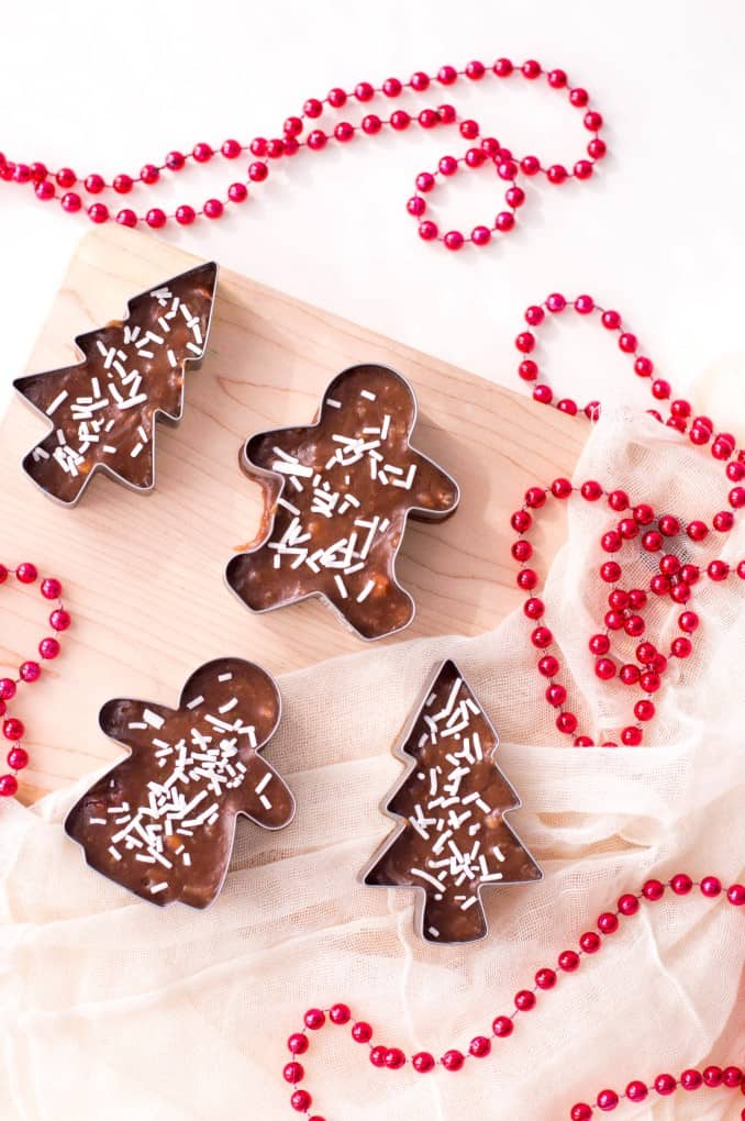 Cookie Cutter Christmas Fudge on a cutting board with red beads.