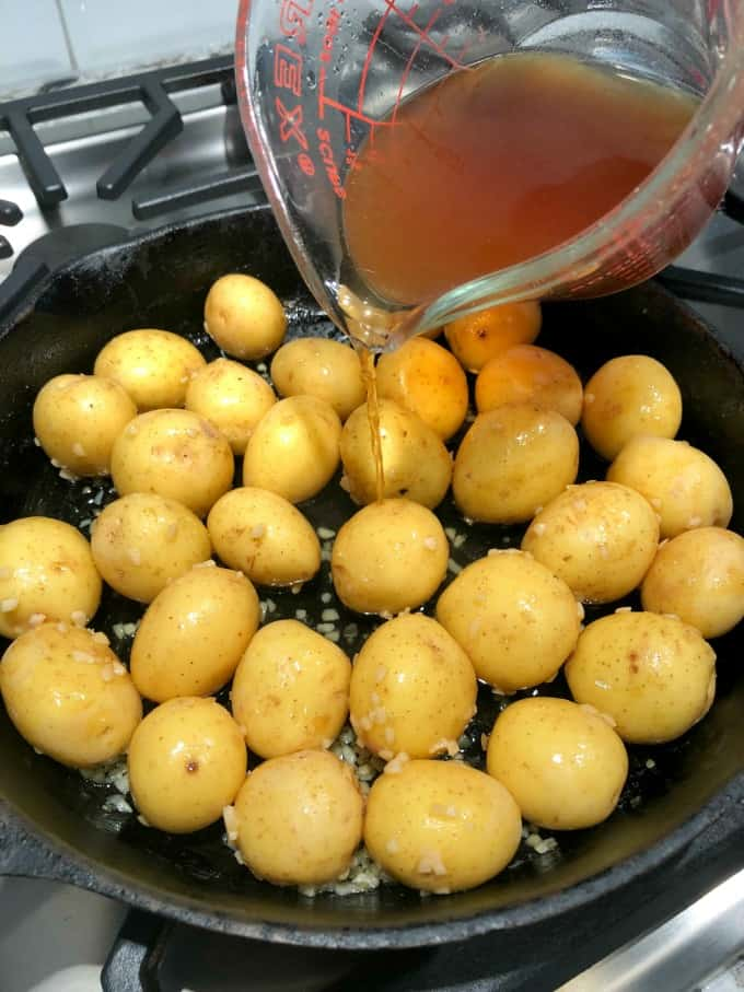 Creamer potatoes in a cast iron pan with beef stock being poured in