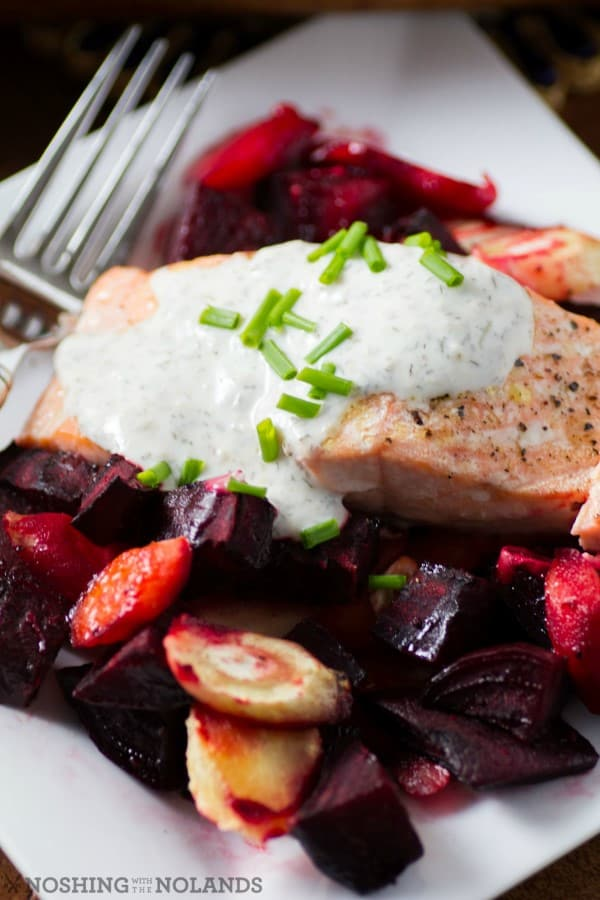 Salmon with horseradish sauce, beets and vegetables on a white plate with a fork