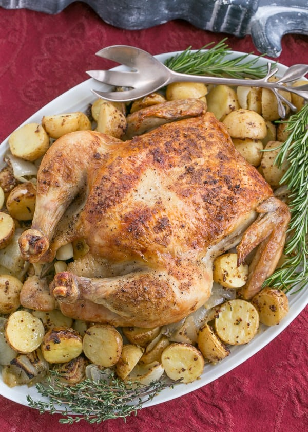 Whole roasted chicken on a platter with potatoes and fresh herbs
