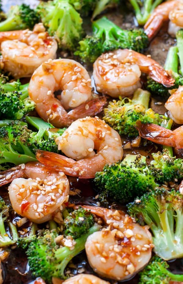 Shrimp and broccoli on a sheet pan with a sauce and sesame seeds