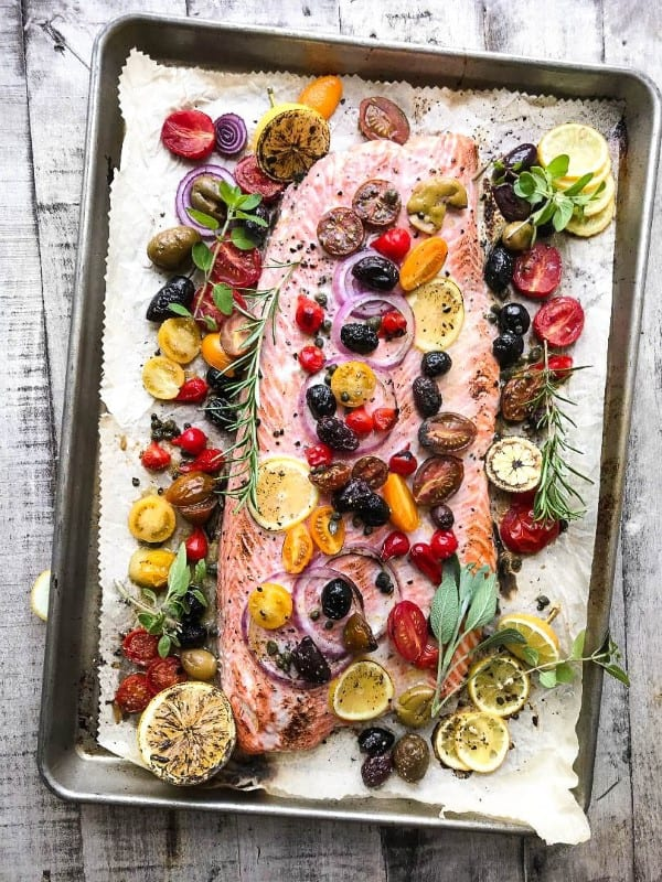 Whole filet of salmon on a sheet pan with olives, tomatoes and herbs