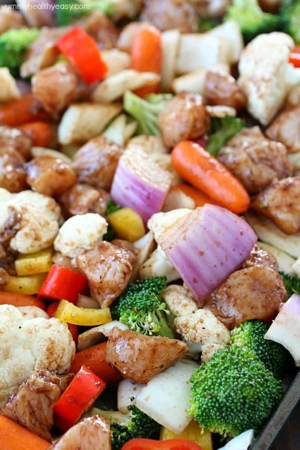 Chopped up chicken and vegetables on a sheet pan