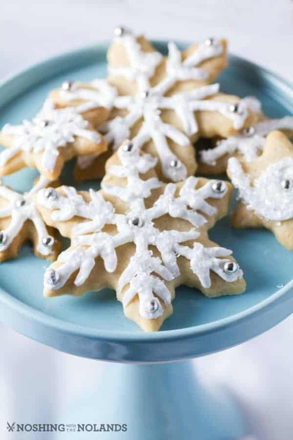 Snowflake Sugar Cookies on a pale blue pedestal.