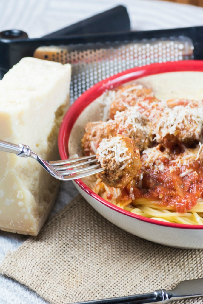 Spaghetti and Meatballs in Marinara Sauce on a fork in a bowl with a block of Parmesan cheese