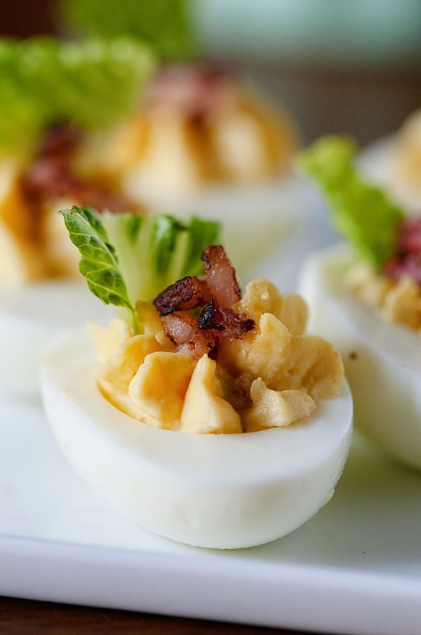 Bacon caesar salad deviled eggs on a white platter