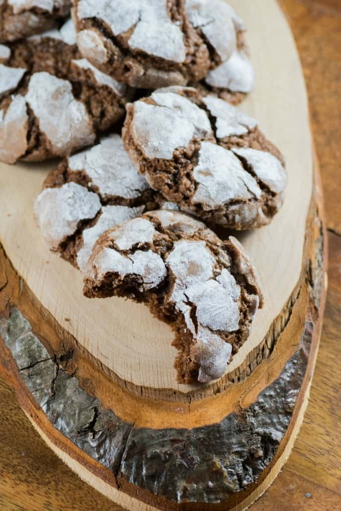 Chocolate Crinkle Cookies on a wooden board, one with a bite taken out.
