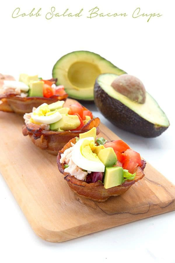 Cobb salad bacon cups on a wooded serving board with a halved avocado