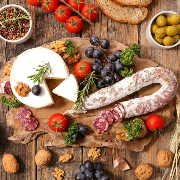 How to build the best charcuterie board various meats, cheeses, fruits olives and nuts on a wooden board