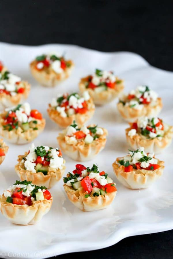 Mini hummus & roasted red pepper phyllo bite on a white serving platter