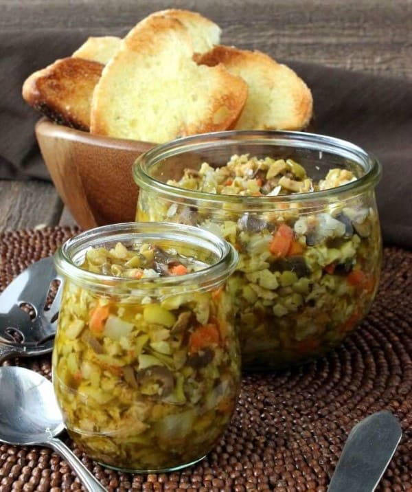 Olive tampenade crostini in a glass jar with the crostini in a wooden bowl