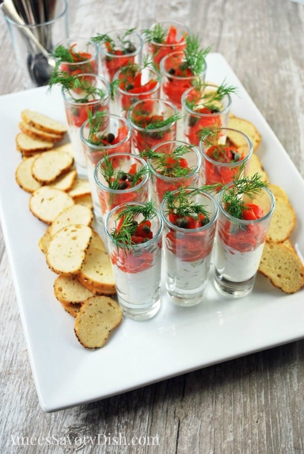 Smoked salmon shooters on a white serving tray with mini toasts