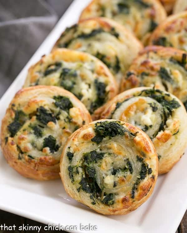 Spinach feta pinwheels on a white serving tray