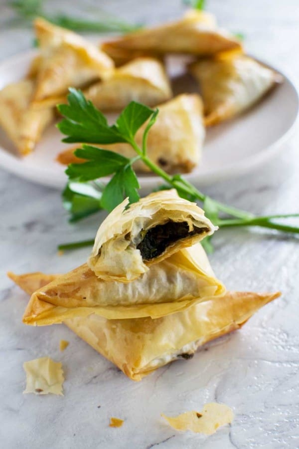 Crispy mushroom filo triangles on a white counter with a white serving tray in the background
