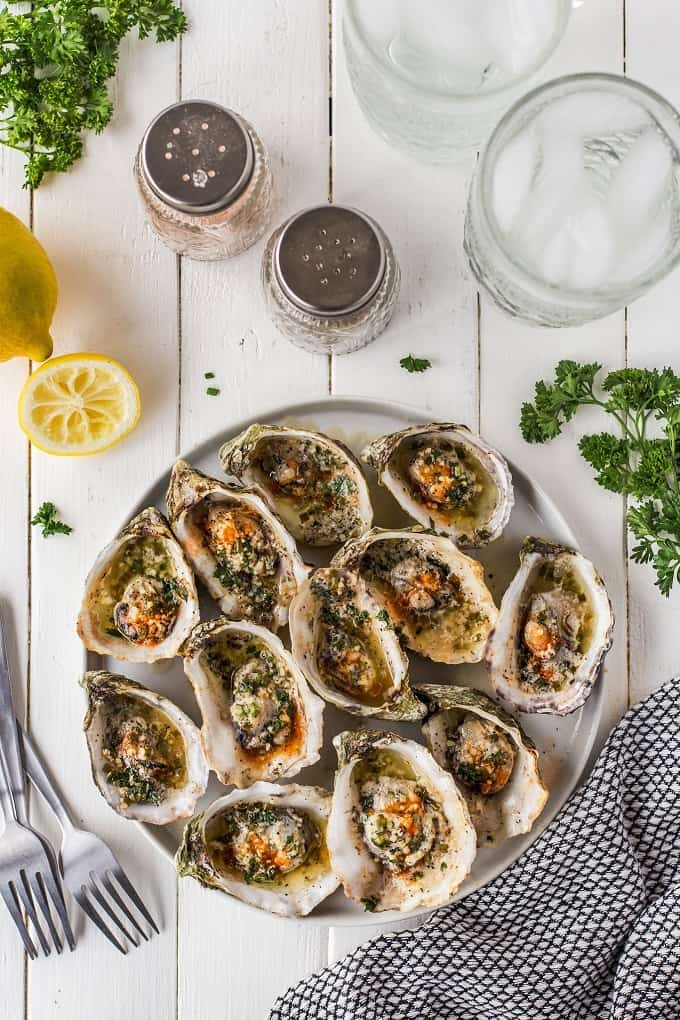 Garlic Herb Butter Grilled Oysters on the half shell on a white serving platter