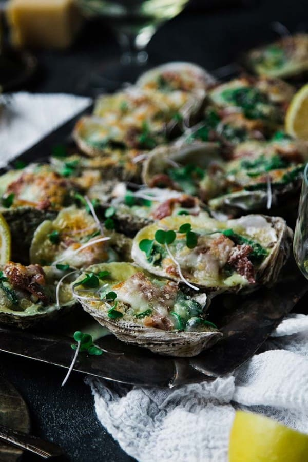 Oysters Rockefeller recipe on a serving tray with lemons