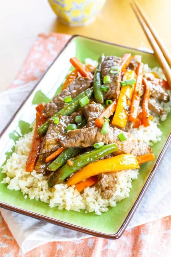 Gluten Free Beef Stir Fry on rice on a green platter with chopsticks