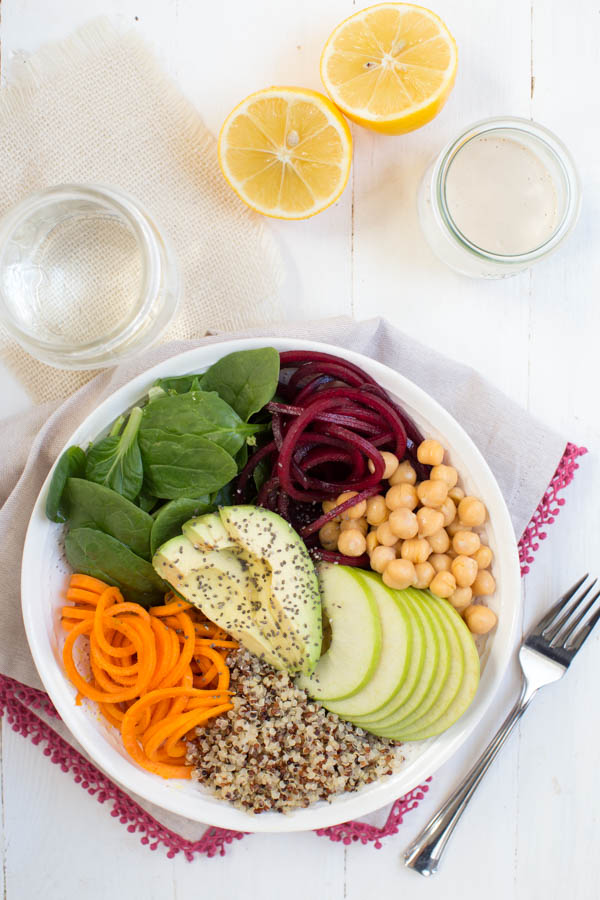 Harvest Buddha Bowl with Lemon Tahini Dressing in a white bowl with fork and glasses