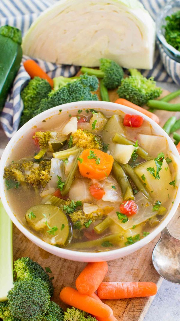Instant Pot Weight Loss Soup in a white bowl surrounded by fresh vegetables.