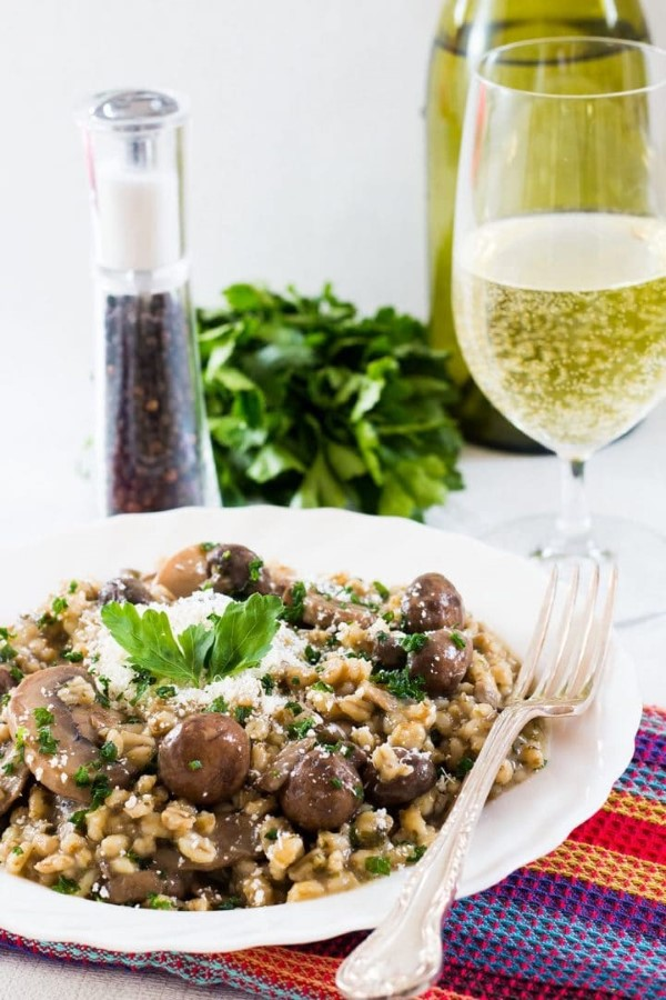 Skinny Mushroom and Barley Risotto in a bowl with fork and glass of white wine