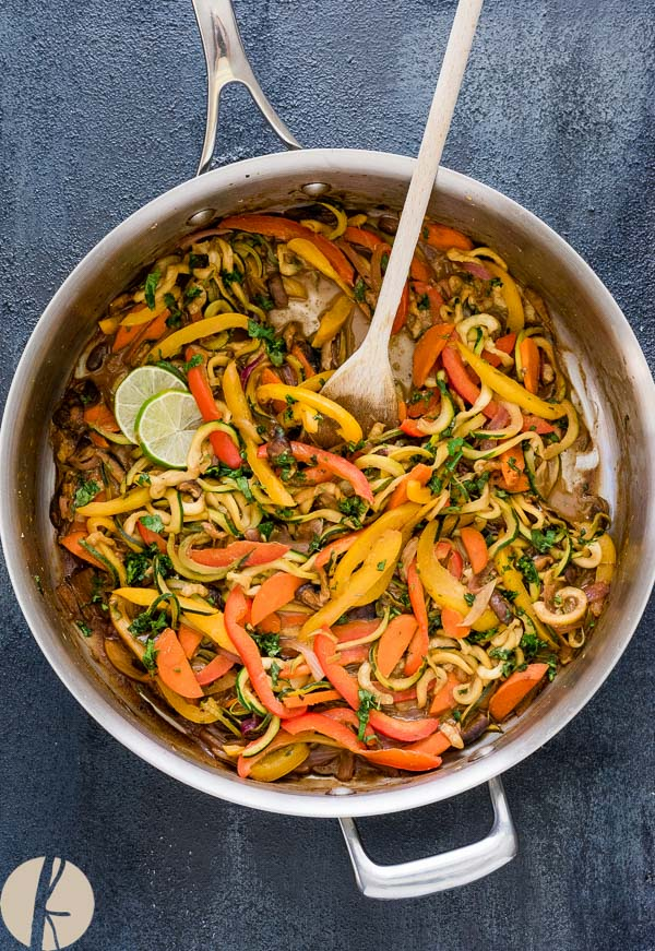 Vegetarian Thai Peanut Zucchini Noodles in a pan with a wooden spoon
