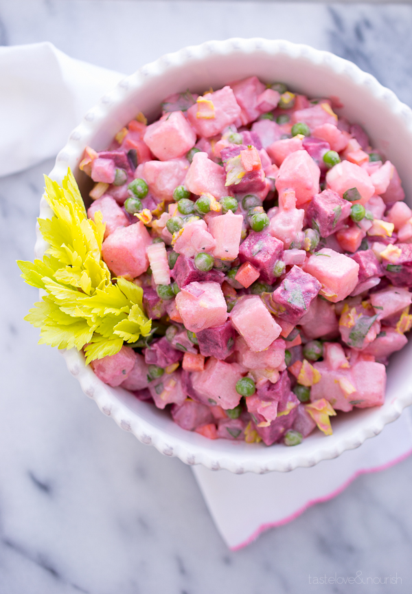 Beet and potato salad in a white serving bowl
