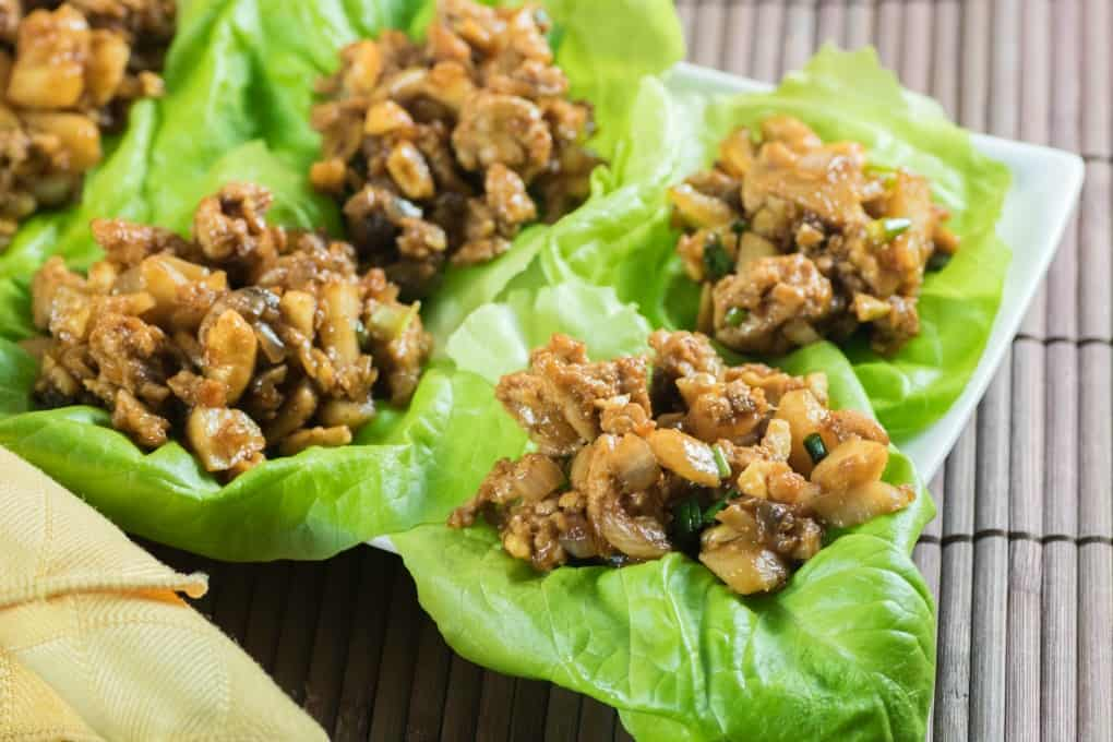 Chicken Lettuce Wraps on a platter on a brown placemat with a yellow napkin.