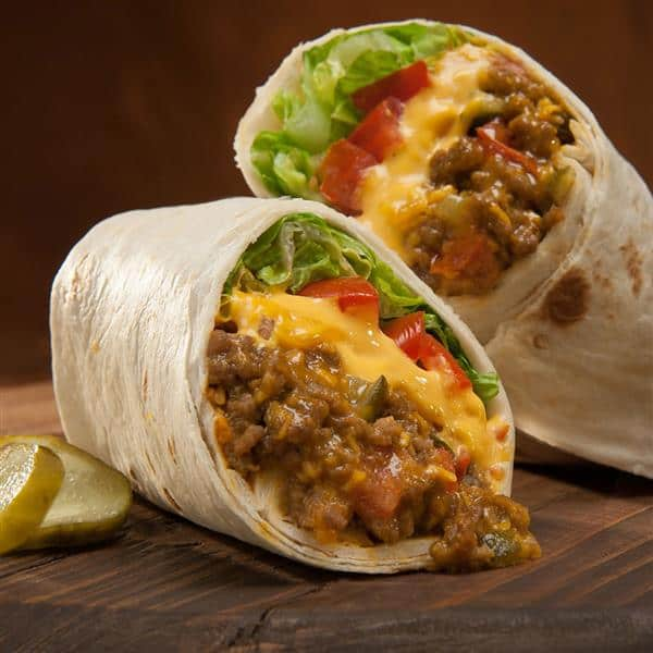 Cheeseburger Burritos cut in half with a dill pickle