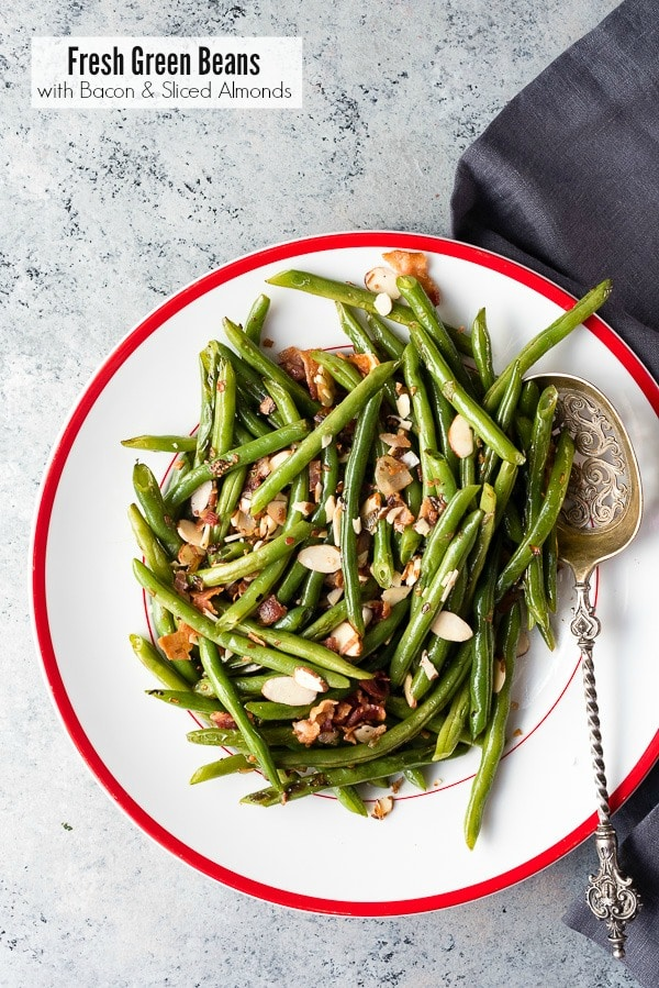 Fresh green beans with bacon and almond slices in a white serving dish and metal serving spoon