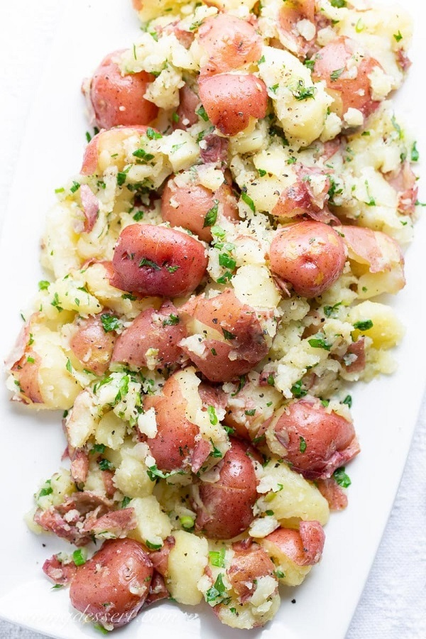 Garlic herb smashed red potatoes on a white serving platter
