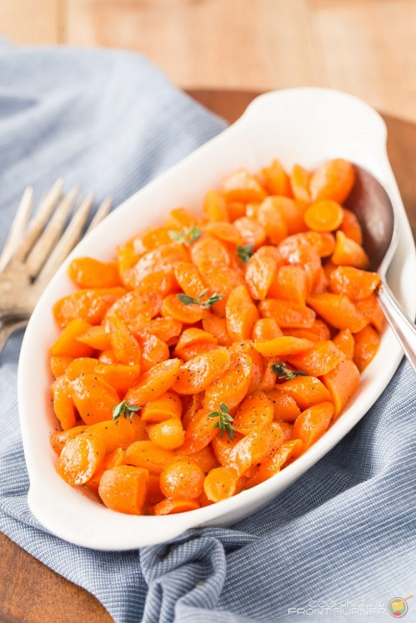 Easy bourbon honey glazed carrots in a white serving dish with a spoon
