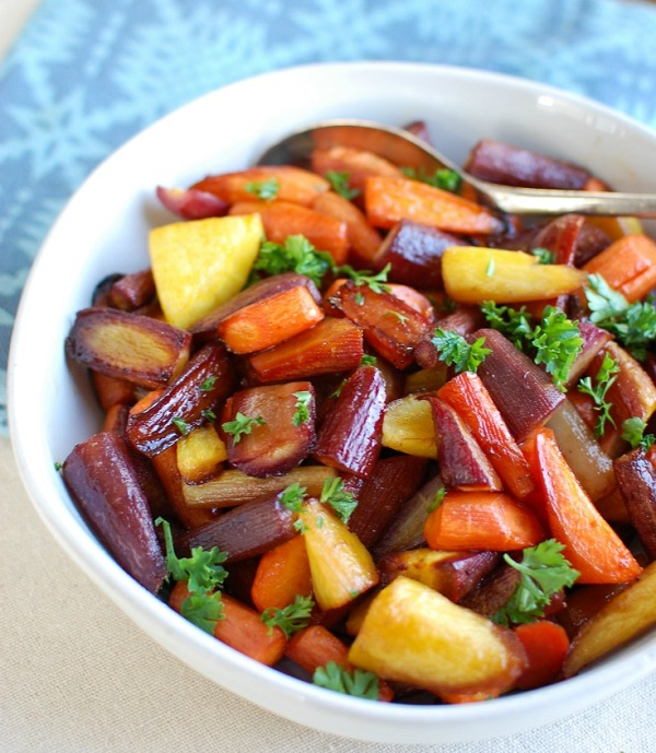 Honey balsamic roasted carrots in a white serving bowl with a serving spoon