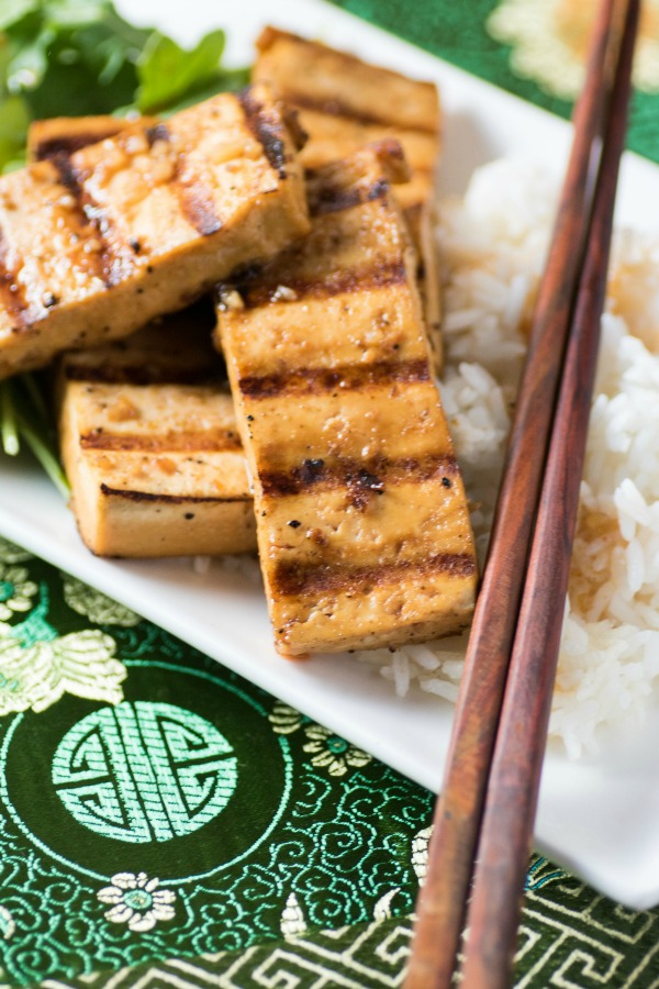 Marinated Grilled Spicy Tofu on a rice with chopsticks on a white platter