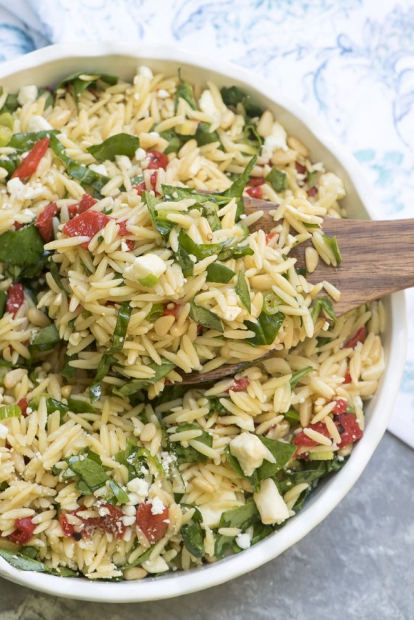 Orzo salad with roasted red peppers, spinach and feta in a white bowl with a wooden serving spoon